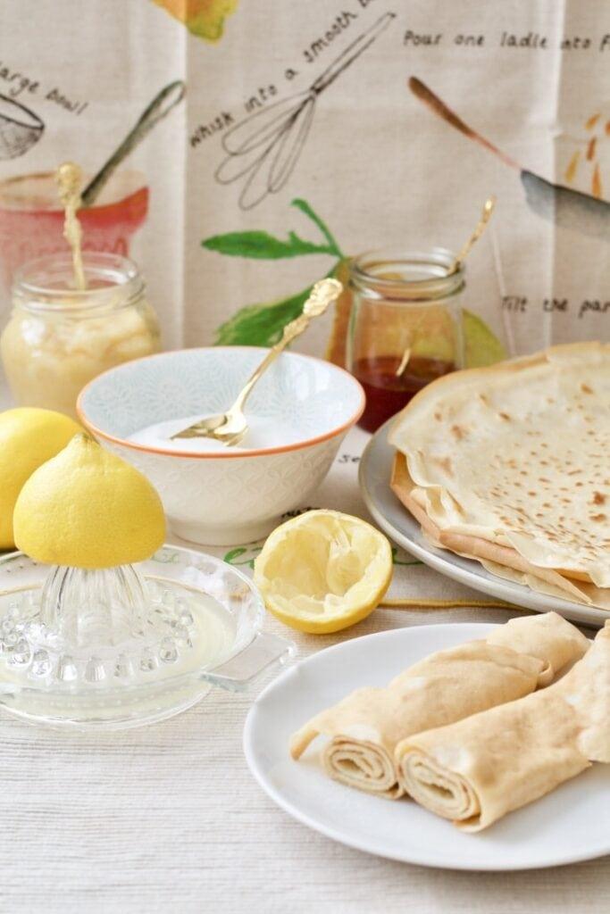 Classic Pancakes - pancakes spread on the table with lemon juice, sugar, jam, lemon curd