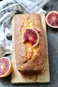 Easy Blood Orange Drizzle Cake on a board decorated with slices of blood oranges.