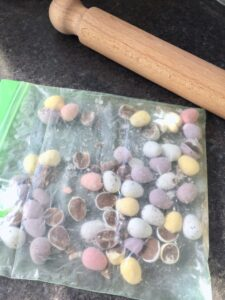 White Chocolate Blondies with Mini Eggs - Mini Eggs in a plastic bag bashed with rolling pin