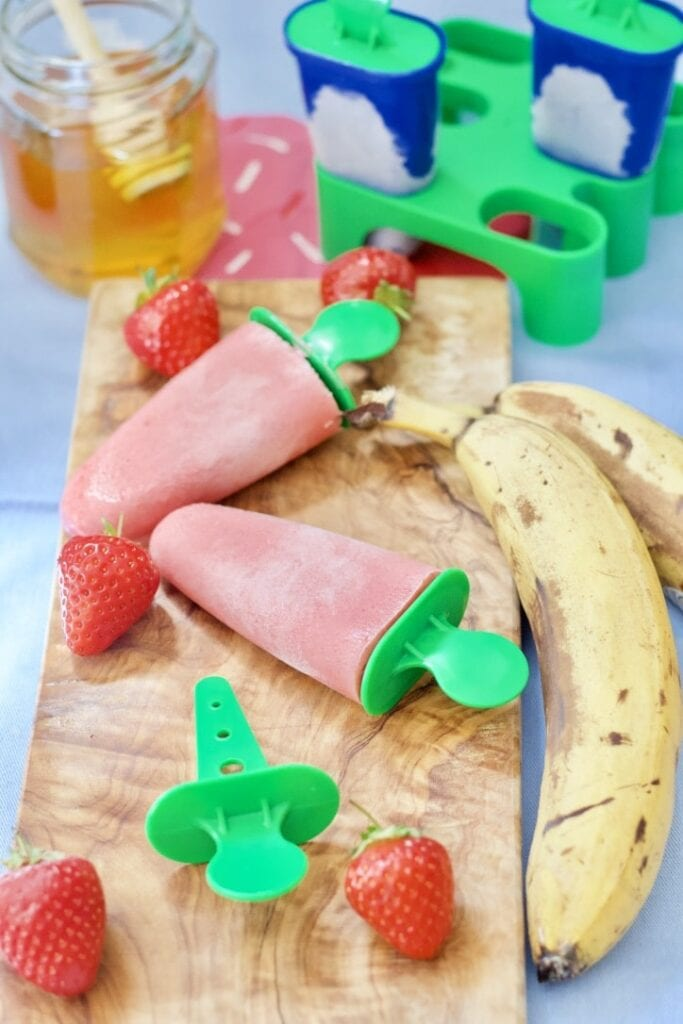 Ice lollies on a wooden board.