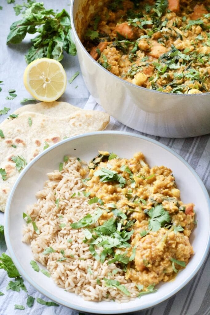 Easy Cauliflower & Lentil Curry - plate of curry and rice standing next to pot full of curry
