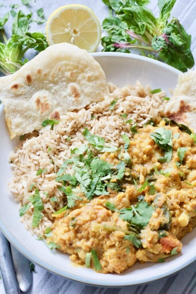 Easy Cauliflower & Lentil Curry - curry plated with rice and flat bread and sprinkled with parsley