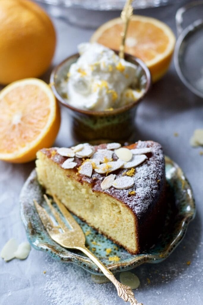 Slice of Gluten-Free Orange and Almond Cake with orange whipped cream and orange halves in the background