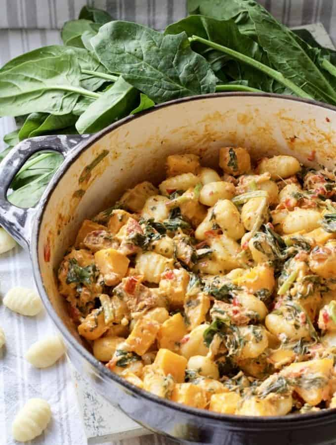 Easy Butternut Squash & Chorizo Gnocchi - close up of pan with ready made dish with some fresh spinach and uncooked gnocchi around it