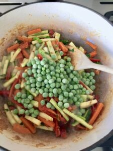 various veggies and frozen peas in a pan