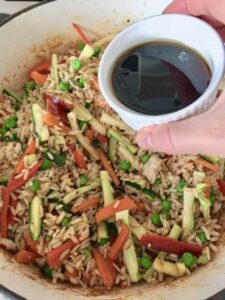 bowl with soy sauce over vegetable egg fried rice