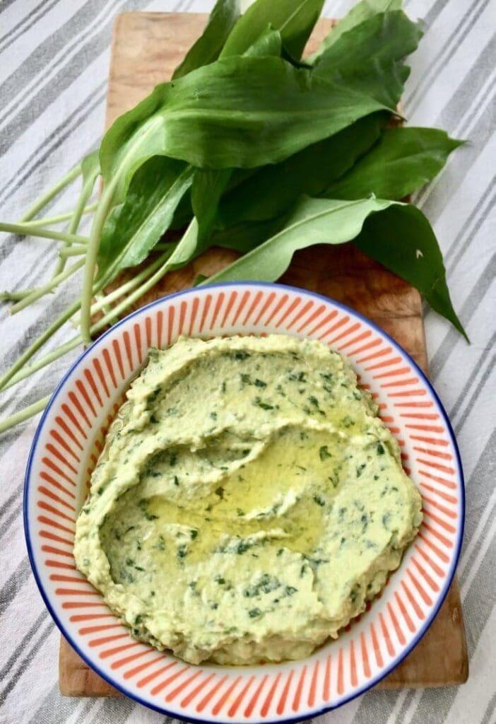 Wild Garlic Hummus in a bowl with fresh wild garlic