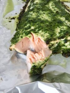 Piece of baked salmon covered in pesto