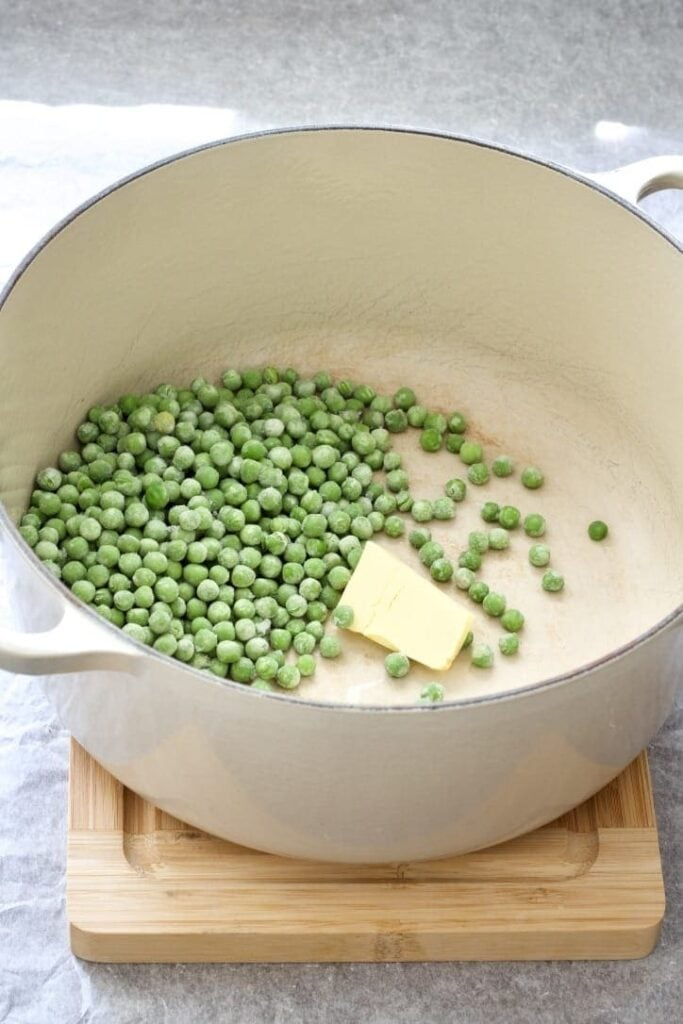 Pot with frozen peas and butter.