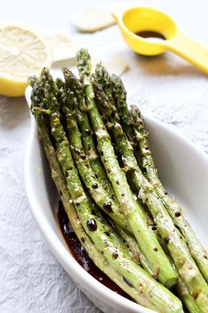 roasted asparagus in a dish with balsamic vinegar