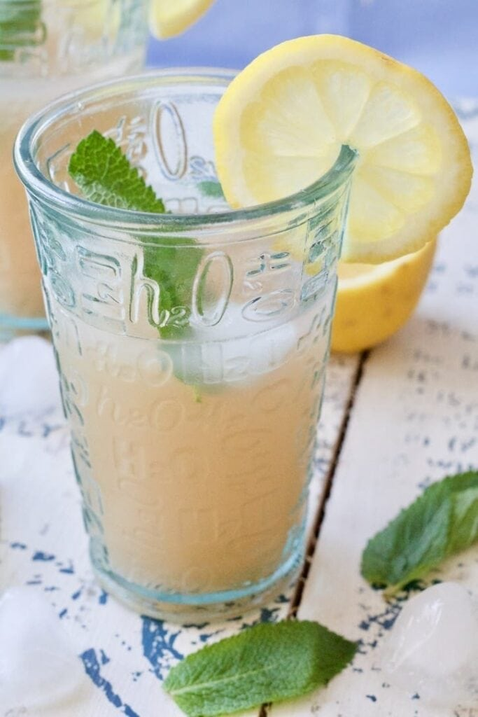 Rhubarb drink in a glass with mint & lemon.