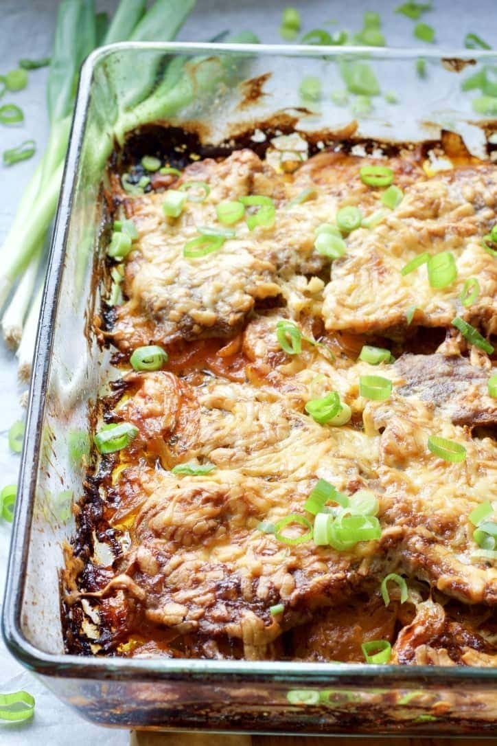 Oven baked pork chops in a baking dish.