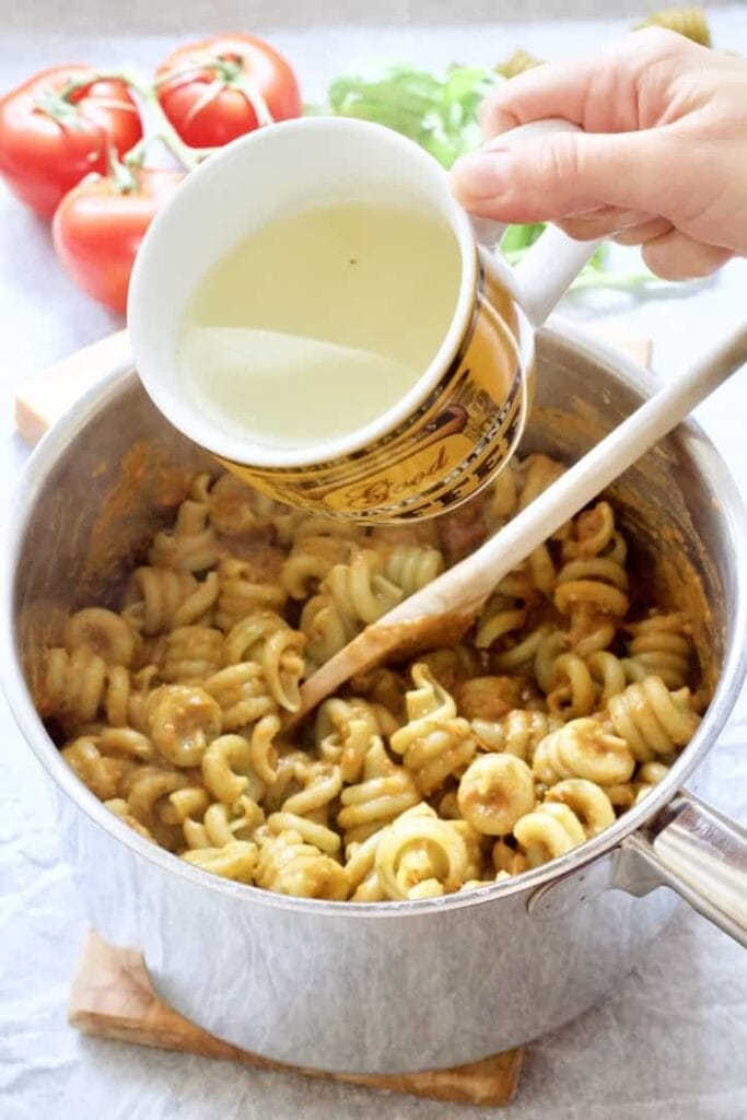 Pasta water being added to pasta sauce.