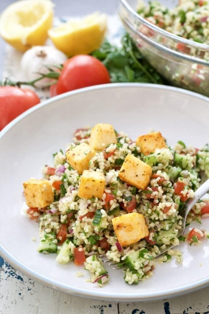 Portion of tabbouleh topped with cheese cubes.