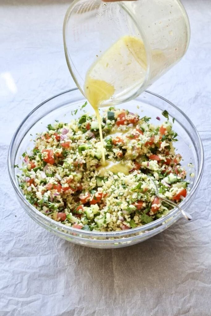 Dressing being poured over the tabbouleh salad.