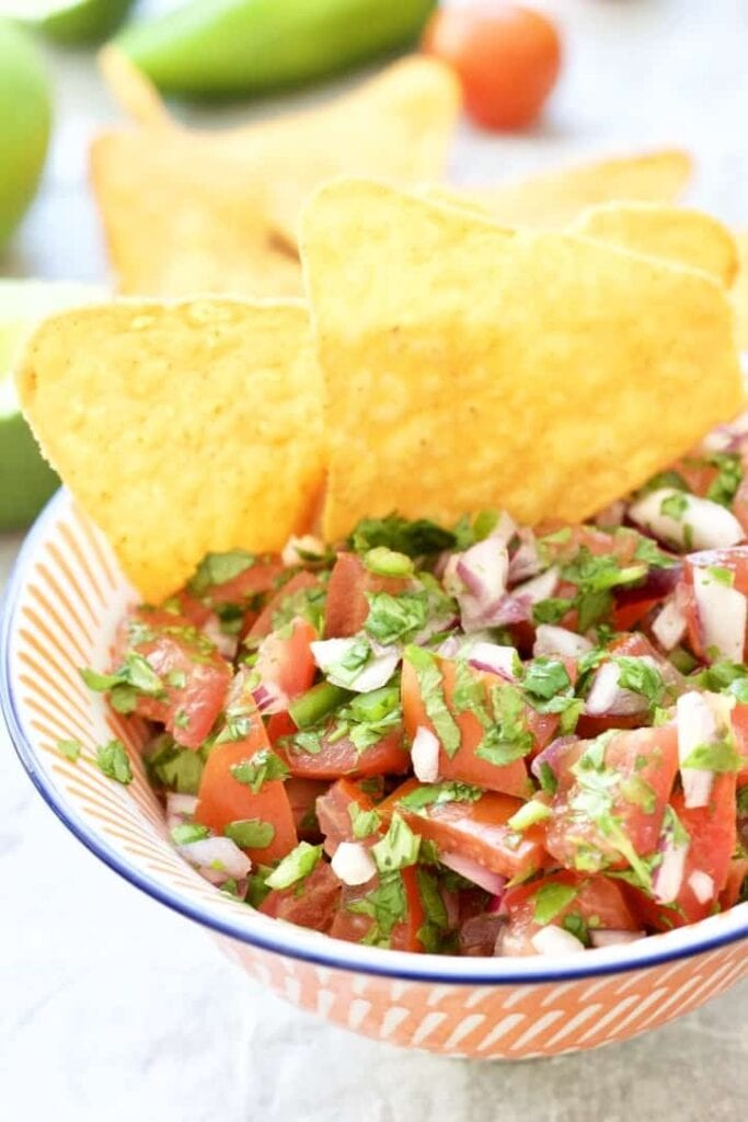 Tomato salsa in a bowl with tortilla chips.