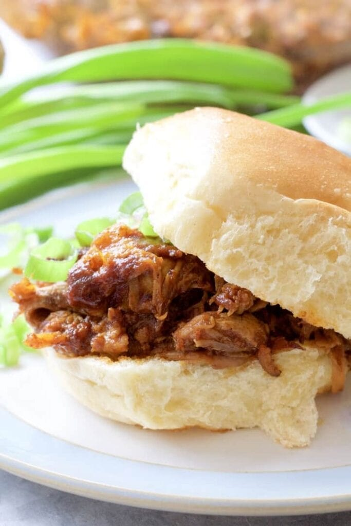 BBQ pulled pork in a bun with top tilted, close up.