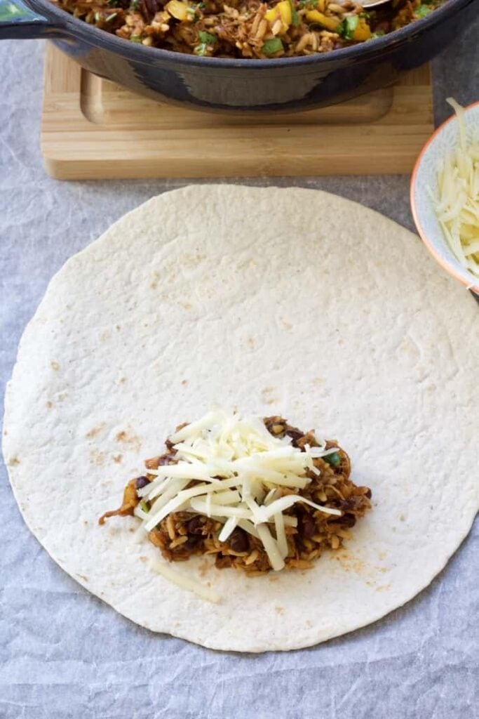 Tortilla with burrito filling and cheese.