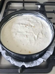 Stem ginger cheesecake in a round cake tin.