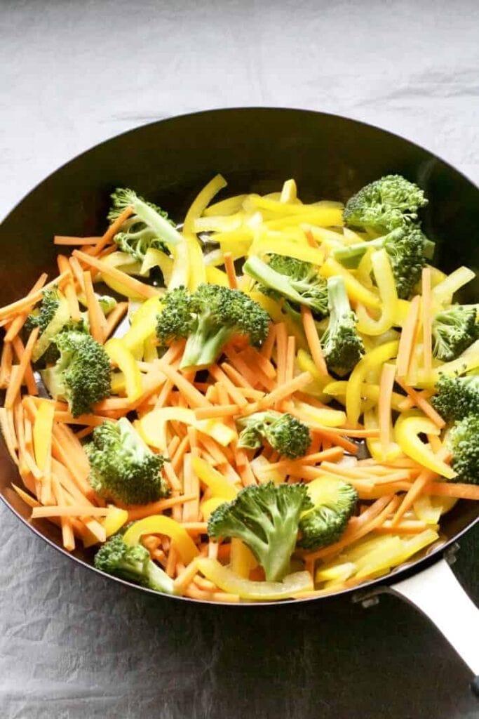 Carrot matchsticks, sliced yellow pepper & broccoli in a pan.