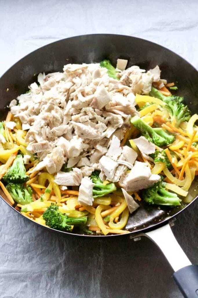 Stir fry veggies and chicken in a pan.