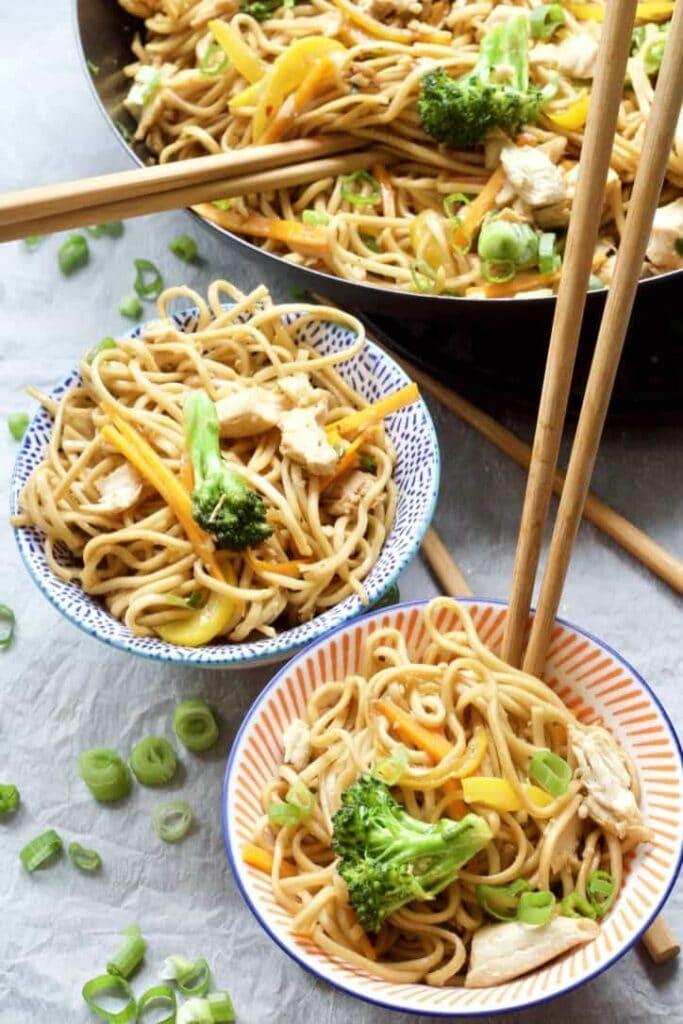 Chicken chow mein in bowls with chopsticks.