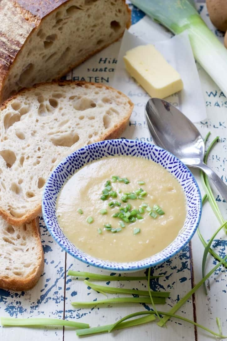 Bowl of leek & potato soup with bread, butter and chives.
